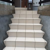 門まわり・玄関アプローチなど、外構工事一式の施工例です。  既存の石積みを左官塗りで仕上げ、階段を設置し、造作で門柱を作成。人工樹木のフェンスとリブロックFを使用して玄関アプローチ一式を施工しました。